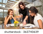 Small photo of Waitress server helping client patron customer with menu order on sunny patio