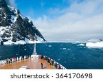 Mountains and cruise ship in Antarctica in sunny day