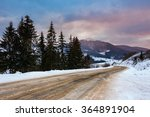 Empty asphalt mountain road under the snow  near the coniferous forest with cloudy sky in winter evening light - stock photo