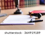 Small photo of Contract waiting for a notary public sign on desk. Notary public accessories