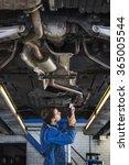 mechanic underneath a car on a... | Shutterstock . vector #365005544