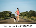 Stock photo sporty woman and dog running together on country road on summer sunset cheerful female athlete 365285360