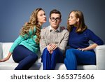 Stock photo a shy young man sitting on the couch with two attractive girls beauty fashion 365375606