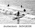 Silhouettes Of Several Surfers...