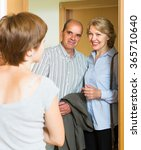 Small photo of Adult daughter greeting elderly parents at threshold
