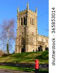 Small photo of WYMESWOLD, ENGLAND - JANUARY 15: St Mary's Church, Wymeswold, with a British red traditional Royal Mail pillar box in foreground. In Wymeswold, England on 15th January 2016.