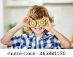 Small photo of Boy having fun with kiwi and holding the fruit in front of his eyes