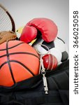 Small photo of sports equipment in a holdall sports bag on a gym floor. football, baseball, cricket, basketball, boxing, squash and a whistle.