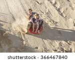 Small photo of Adventuresome girls boarding down the Sand Dunes