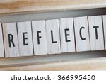 Small photo of REFLECT word written on wooden