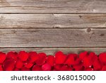 Stock photo red rose petals over wooden background top view with copy space 368015000