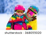 mother and little child skiing... | Shutterstock . vector #368055020