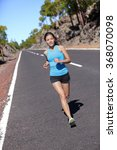 Small photo of Female road runner training running in outdoor nature. Asian woman jogging fast working out her cardio in blue top and black shorts activewear.