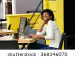 Small photo of Portrait of an african american woman laughing with laptop at cafe