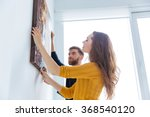 happy couple hanging picture on ... | Shutterstock . vector #368540120