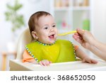 baby eating food on kitchen | Shutterstock . vector #368652050