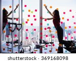 Small photo of Mixed race secretary working in modern office in skyscraper, sticking adhesive notes with tasks on window. The girl feels stressed and overwhelmed