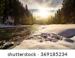 frozen river among conifer forest with snow on the ground in carpathian mountains in evening light - stock photo
