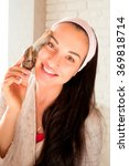 Small photo of portrait of young smiling darkhaired woman with snails achatina giant on her face