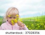 little girl smelling  flower... | Shutterstock . vector #37028356