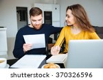 happy young couple calculating... | Shutterstock . vector #370326596