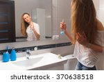 young woman applying hairspray... | Shutterstock . vector #370638518