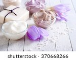 Small photo of cosmetic cream variations, soap and autumn crocus herbal flower on white wooden table