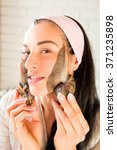 Small photo of portrait of young darkhaired woman with snails achatina giant on her face