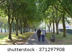 Small photo of TROWBRIDGE, UK - OCT 14, 2015: A couple walk through a public park on Oct 25, 2015 in Trowbridge, UK. The UK experiencing an 'Indian Summer' with above average temperatures and stunning fall colours.