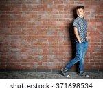 cute little boy on brick wall... | Shutterstock . vector #371698534