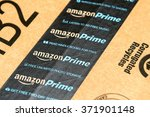 Small photo of PARIS, FRANCE - JAN 28, 2016: Amazon Prime logotype printed on cardboard box security scotch tape. Amazon Prime is a service from Amazon which delivers parcels in 1 day, streams unlimited music