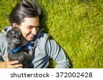 Stock photo little pet dog and his owner having fun outdoors 372002428