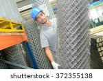 man holding roll of metal... | Shutterstock . vector #372355138