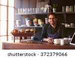 Stock photo portrait of male coffee shop owner standing behind counter 372379066
