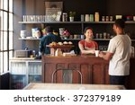 staff serving customer in busy... | Shutterstock . vector #372379189