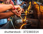 lighting incense to buddha. | Shutterstock . vector #372383314