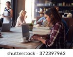 Stock photo interior of coffee shop with customers using digital devices 372397963