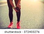 woman runner hold her injured... | Shutterstock . vector #372403276