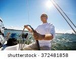 Senior Man At Helm On Boat Or...