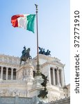 Small photo of View of Italian national flag in front of Altare della Patria (Altar of the Fatherland) , the equestrian sculpture of Victor Emmanuel and statue of the goddess Victoria riding on quadrigas on top