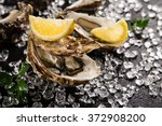 fresh oysters on a black stone... | Shutterstock . vector #372908200