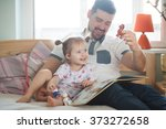 dad and daughter reading a book | Shutterstock . vector #373272658