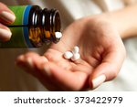 a young woman pours the pills... | Shutterstock . vector #373422979
