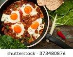 shakshuka is a dish of eggs... | Shutterstock . vector #373480876