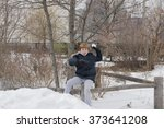 Young boy sitting on a wooden fence preparing to throw a snowball - stock photo