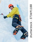 Small photo of Athletic alpinist man in orange helmet and ice tools axe climbing a large wall of ice. Outdoor Sports Portrait