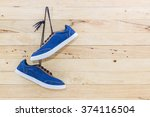 Blue Sneakers Hang On A Nail O...