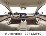 Car interior luxury. Beige comfortable seats, steering wheel, dashboard, climate control, speedometer, display, wood decoration & orange ambient light - stock photo