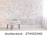 White Armchair On Brick Wall...