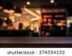Stock photo empty top of wooden table or counter on cafeteria bar coffee shop background for product display 374554153